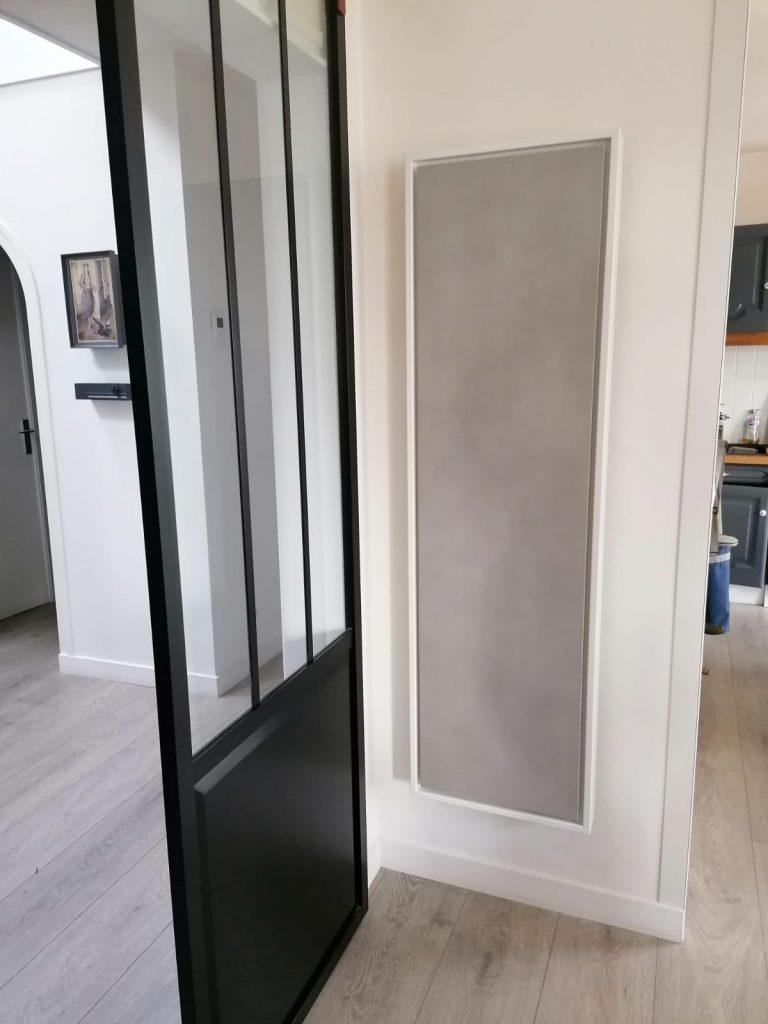 Radiateur à inertie vertical design eternity de 1500w. Format vertical, couleur gris clair, 155 par 45cm, il est dans une pièce de vie.