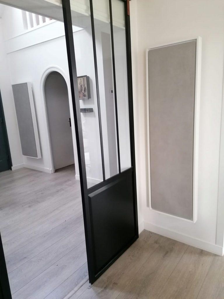 Photo de 2 radiateurs électriques à inertie design gris clair, l'un de 2400w en 155x60cm, l'autre de1500w en 155x45cm. Les 2 sont verticaux et sont situés dans un hall et pièce de vie d'une maison