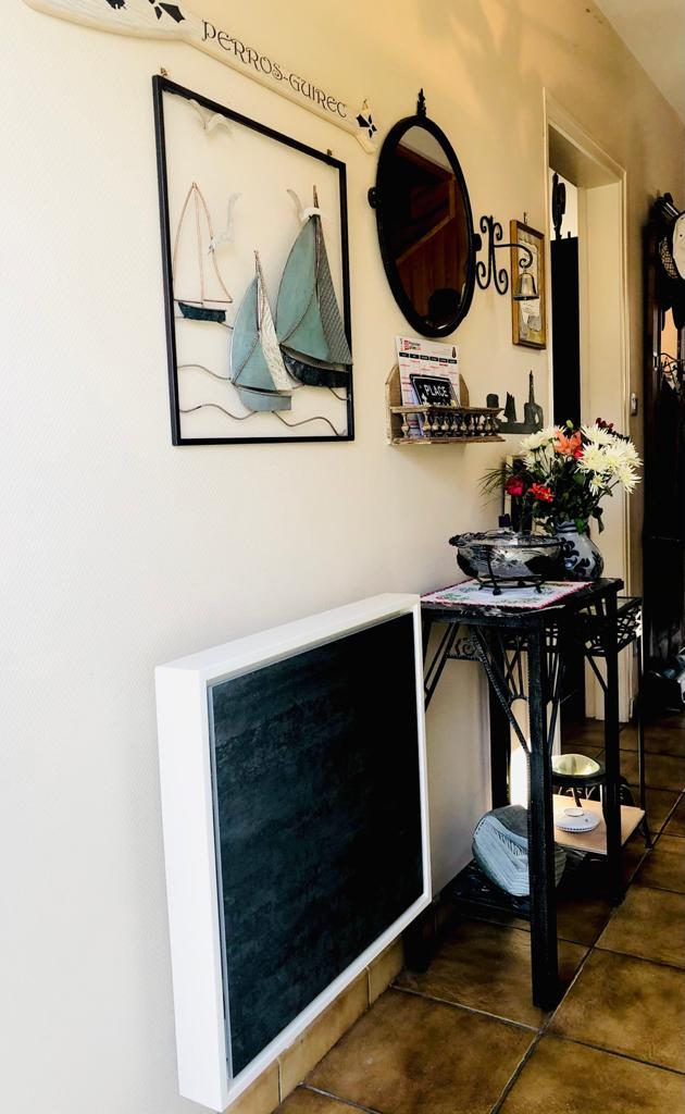 Photo d'un radiateur éco-électrique décoratif Eternity. Il s'agit ici d'un format économique de 100w, aux dimensions 60x65cm, de couleur anthracite, installé dans une maison